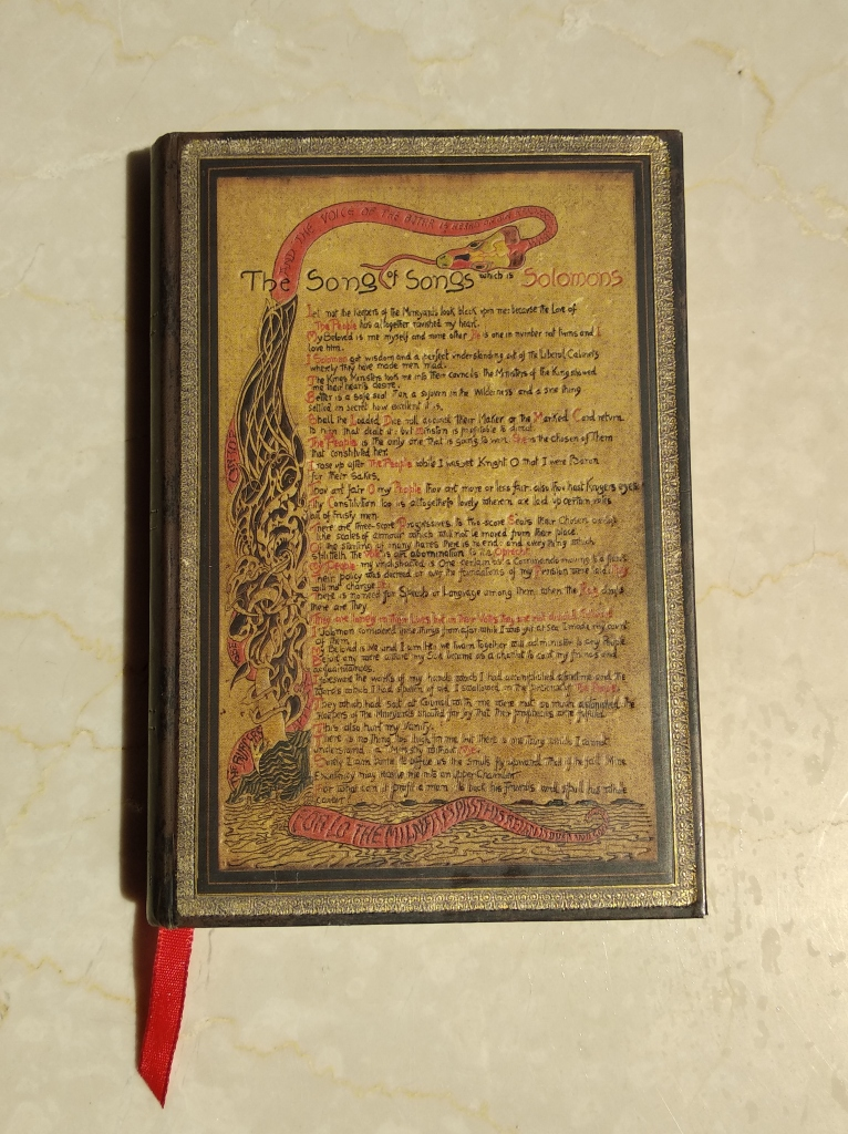 "Small notebook with an embellished cover that depicts the illustrated letter ""The Song of Songs which is Solomon's"" by Rudyard Kipling."