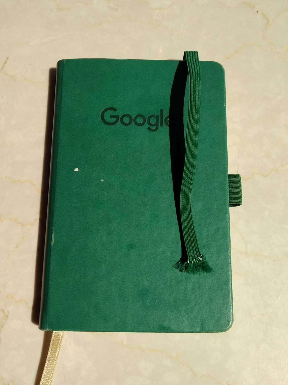 A dark green notebook with the Google logo.