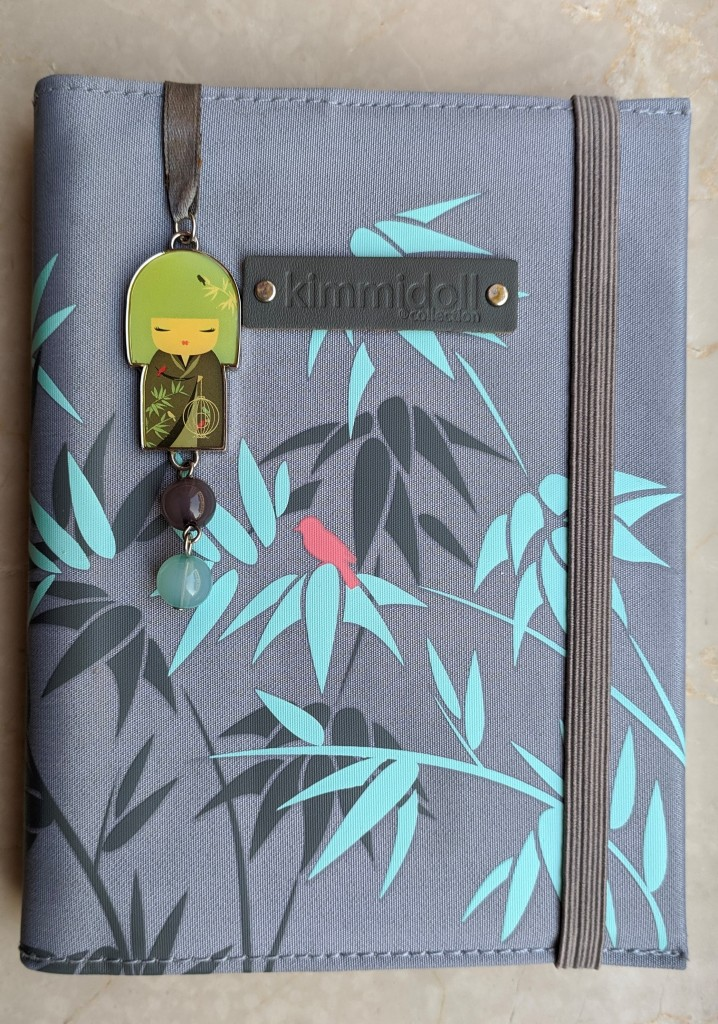 Kimmidoll notebook with a grey cover with green plants and a pink bird. There is a grey ribbon bookmark attached, and at the end it has a kimmidoll wearing a kimono with the notebook's pattern.
