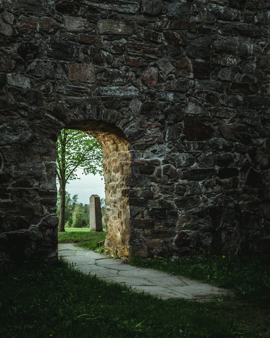 A stone archway opening to a cemetery.