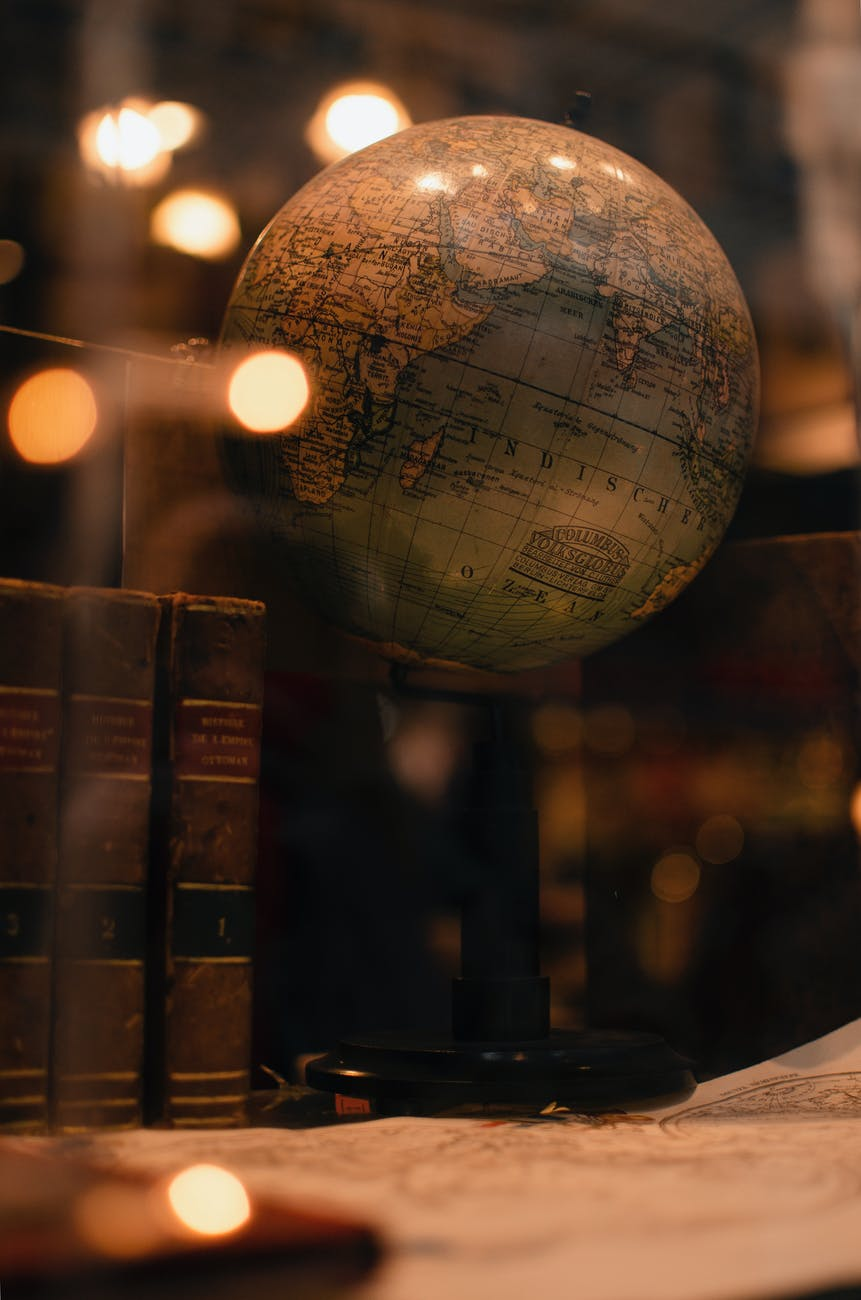 A blurry image of a globe surrounded by old books and maps.