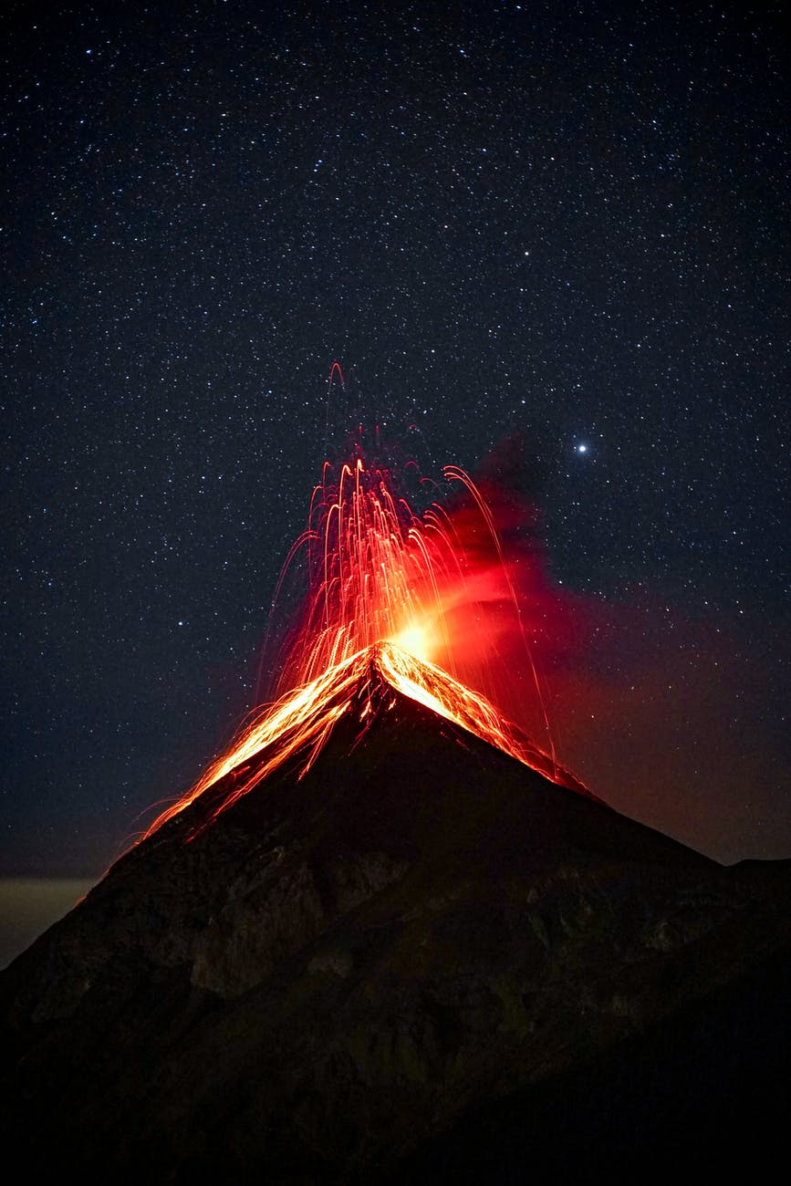 Volcano erupting against a starry sky.
