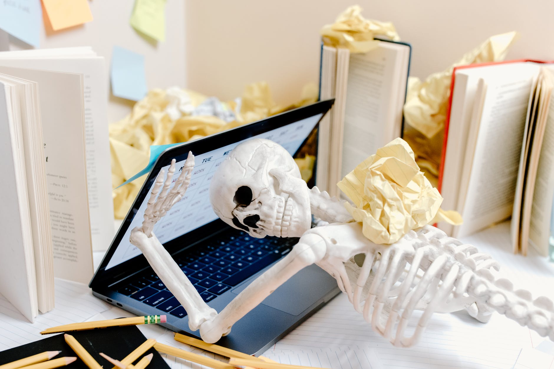 There's a Halloween skeleton covered in papers and being attacked by a laptop. The skeleton is trying to push the laptop open, but the laptop is closing over the skeleton's head. The skeleton is looking towards us, making it seem like there's a look of desperation in its face.
